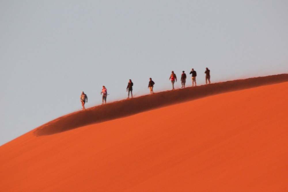 Walking the ridge of Dune 45 in the Namibia Desert at sunrise